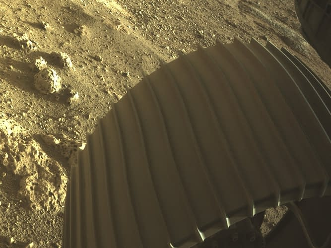 Photo of the Mars rover Perseverance's wheel and rocks on the surface.
