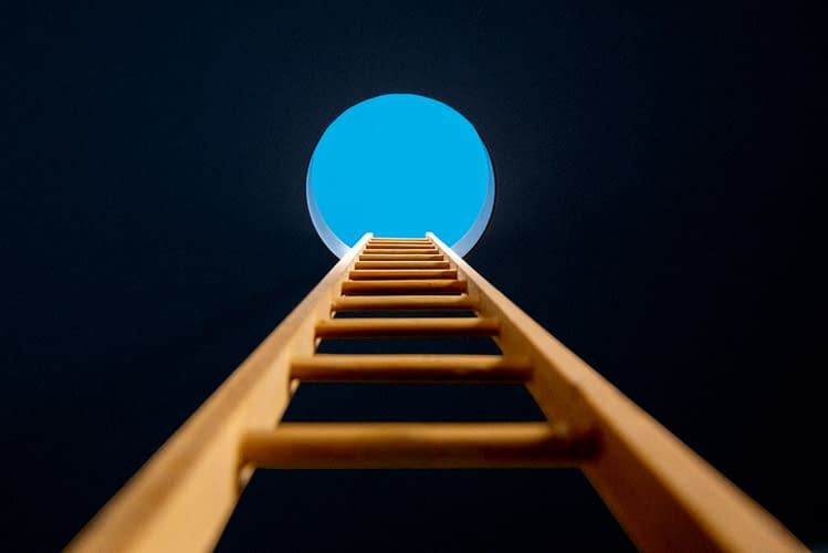 Point of view, looking up ladder sticking through hole in ceiling revealing blue sky