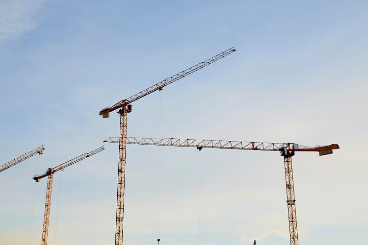 Cranes of a construction site against blue sky