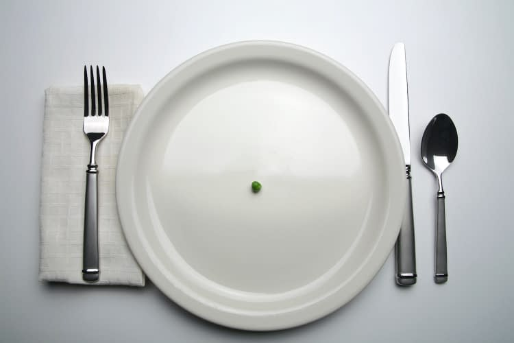 Suggesting scarcity, a single green pea rests in the middle of a dinner plate surrounded by tableware.