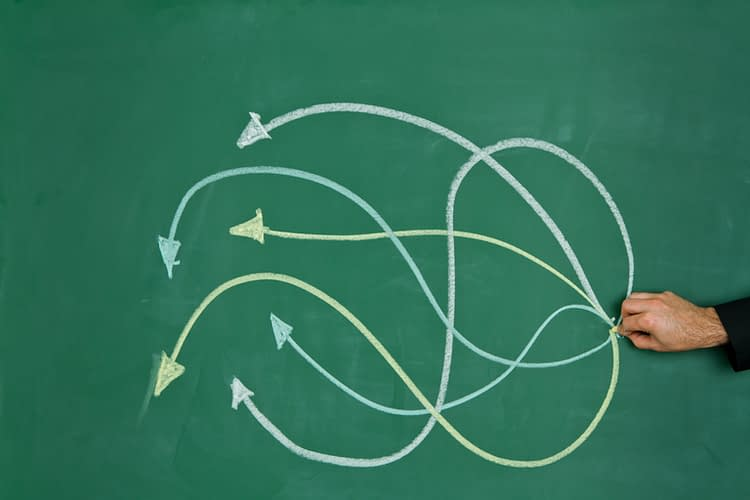 Image of intertwining arrows on a chalkboard to represent decision-making.